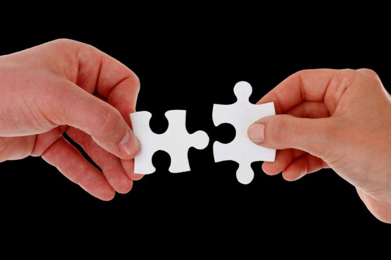 Man and woman holding a puzzle piece each